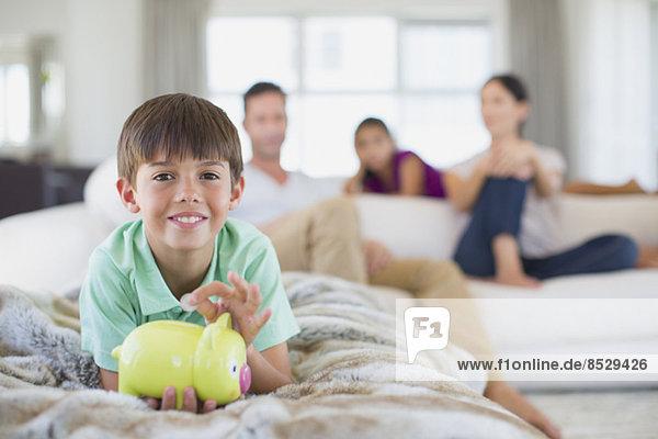 Junge mit Sparschwein auf Sofa im Wohnzimmer