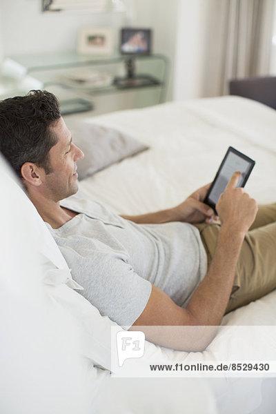 Mann mit digitalem Tablett auf dem Bett