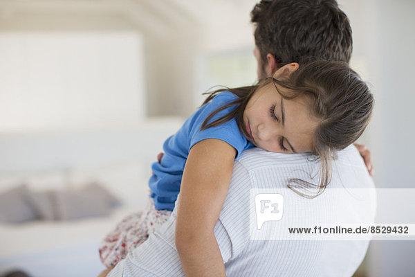 Vater mit schlafender Tochter