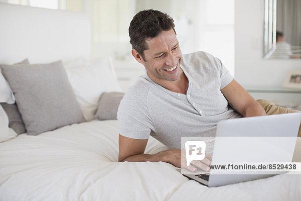 Mann mit Laptop im Bett