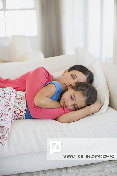 Mother and daughter napping on sofa in living room
