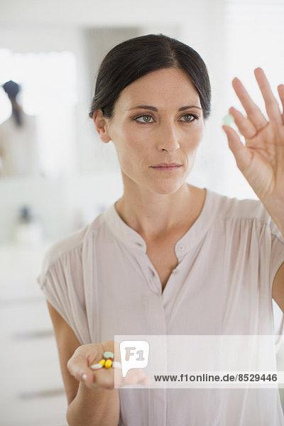 Frau untersucht Pillen im Bad