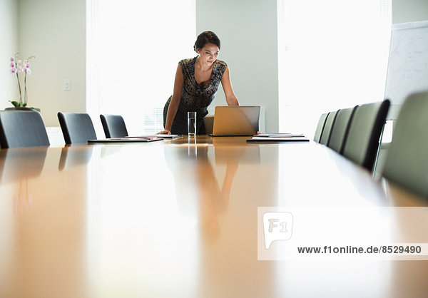 Geschäftsfrau mit Laptop am Konferenztisch