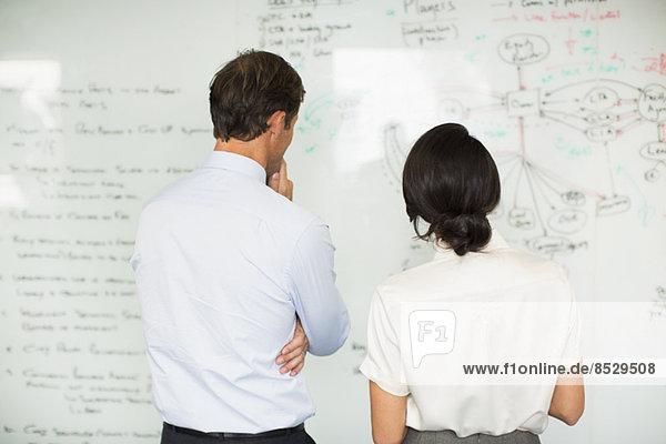 Geschäftsleute lesen Whiteboard im Büro