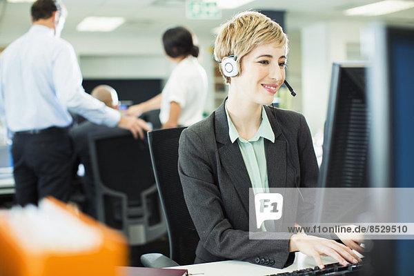 Geschäftsfrau spricht am Headset im Büro