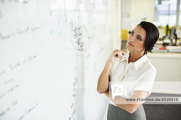Geschäftsfrau beim Blick auf Whiteboard im Büro