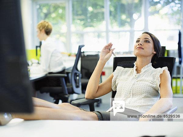 Geschäftsfrau entspannt mit den Füßen auf dem Schreibtisch im Büro