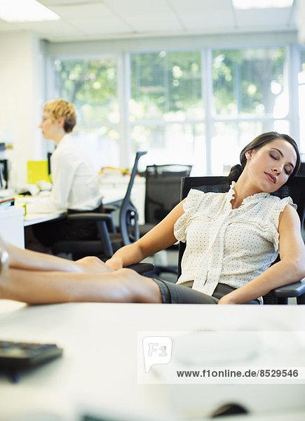 Geschäftsfrau schläft am Schreibtisch im Büro