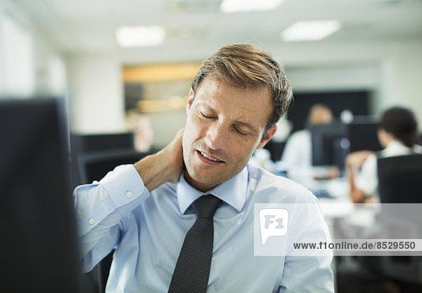 Geschäftsmann reibt sich im Büro den Hals.