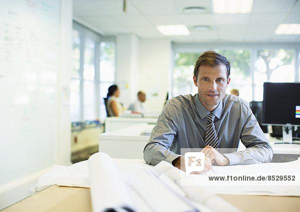 Geschäftsmann beim Lesen von Bauplänen im Büro