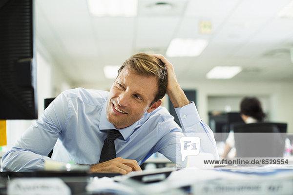 Geschäftsmann schielend am Schreibtisch im Büro