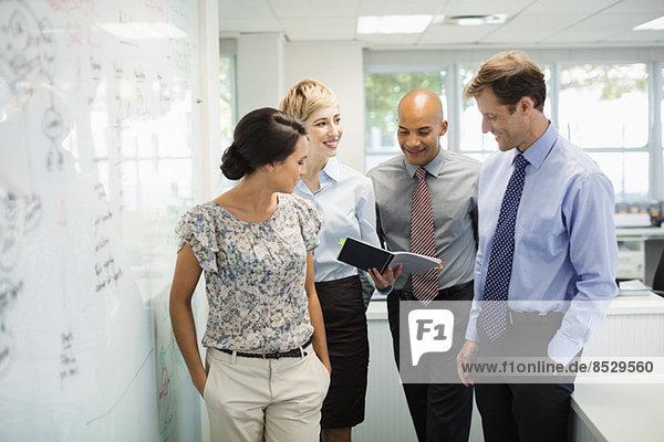 Geschäftsleute sprechen am Whiteboard im Büro