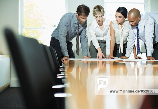 Geschäftsleute bei der Prüfung von Bauplänen im Meeting