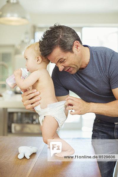 Vater prüft Babywindel