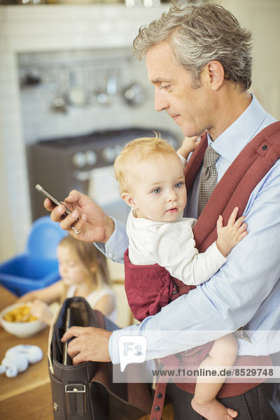 Father holding baby and checking cell phone