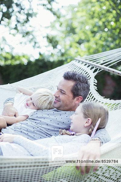 Vater und Kinder entspannen in der Hängematte