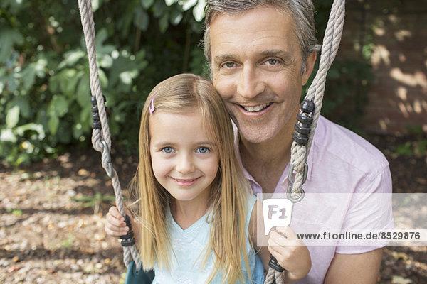 Vater schiebt Tochter auf Schaukel