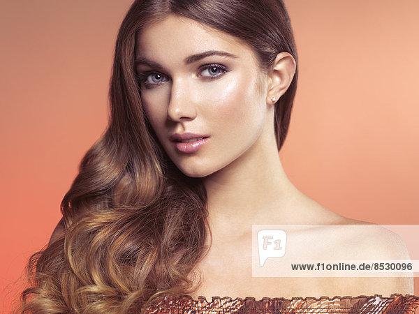 Woman with long wavy brown hair and natural makeup