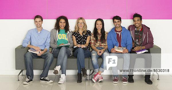 Universitätsstudenten lächeln auf der Bank