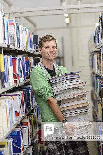 Student mit Bücherstapel in der Bereichsbibliothek der Universität Hohenheim  Stuttgart  Baden-Württemberg  Deutschland