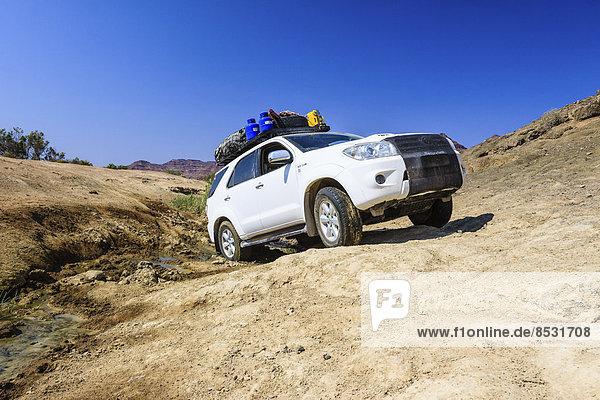 Geländewagen fährt durch den Schlamm am Fluss Huab  Damaraland  Namibia