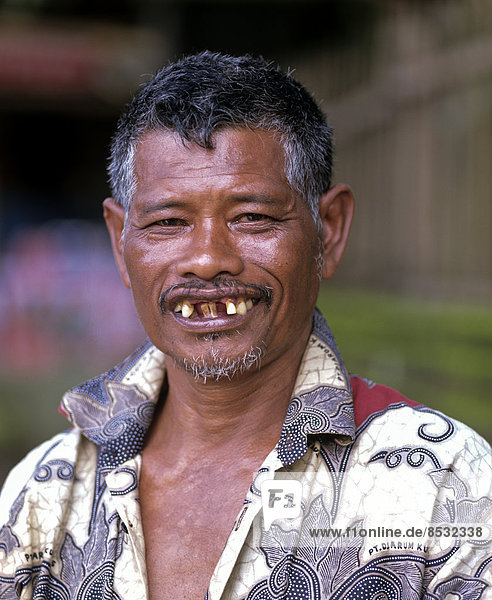 Balinese man smiling with bad teeth  tooth loss  Bali  Indonesia