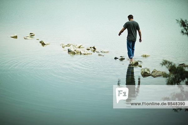 Ein Mann  der barfuß über Trittsteine vom Ufer eines Sees weggeht.