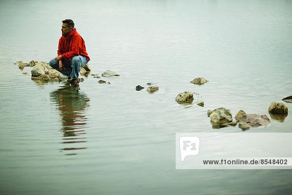 Ein Mann in einer roten Jacke balanciert in einer nachdenklichen Pose auf einem Trittstein oder Felsen im flachen Wasser.