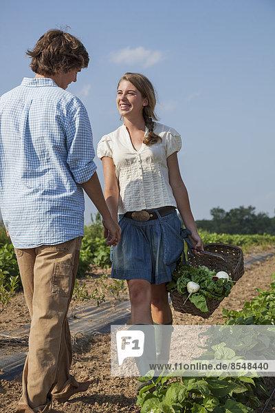 Ein Mädchen führt einen Jungen an der Hand auf einem Feld  auf dem Gemüse und Pflanzen angebaut werden.
