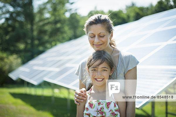 Ein Kind und seine Mutter an der frischen Luft  neben Sonnenkollektoren an einem sonnigen Tag auf einer Farm im Staat New York  USA.