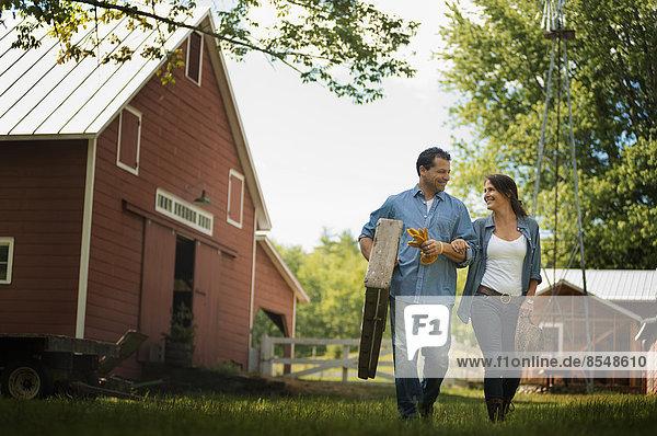 Zwei Menschen  Mann und Frau auf dem Hof eines traditionellen Bauernhofs in den USA.