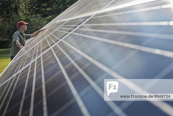 Ein Mann inspiziert die Oberfläche einer großen  geneigten Solarpaneelanlage zur Nutzung der Sonnenenergie.
