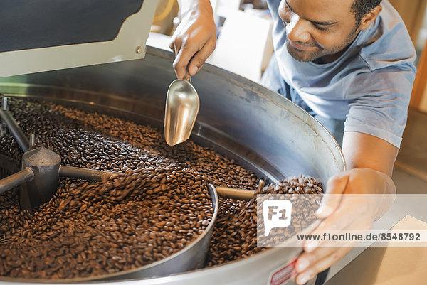 Maschinen in einer Kaffeebohnenverarbeitungshalle  in der die Bohnen erhitzt und geröstet werden  werden von einem jungen Mann beaufsichtigt.