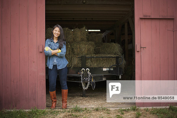 A young woman on a traditional farm in the countryside of New York State  USA