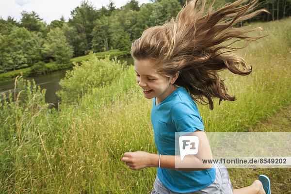 Ein junges Mädchen rennt auf einem Pfad an einem See entlang  die Haare fliegen ihr hinterher. Ein junges Mädchen rennt auf einem Pfad an einem See entlang, die Haare fliegen ihr hinterher.