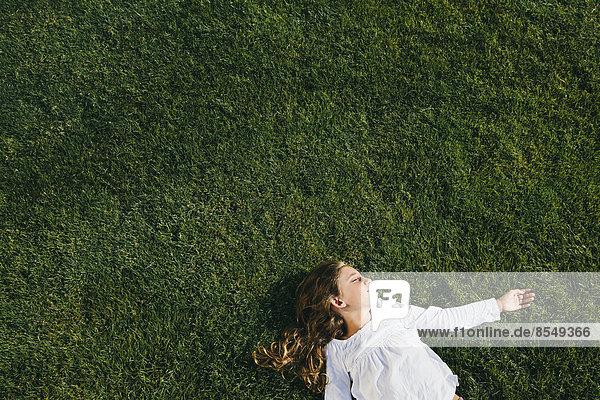 Neunjähriges Mädchen lächelt und ruht sich auf einem Feld aus saftigem  grünem Gras aus