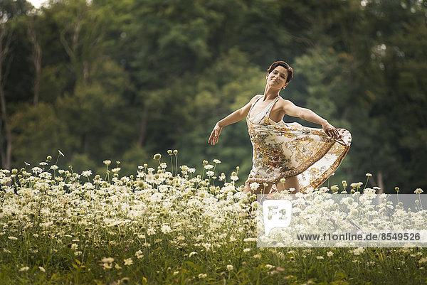 Eine Frau tanzt auf einem Feld mit Wildblumen.