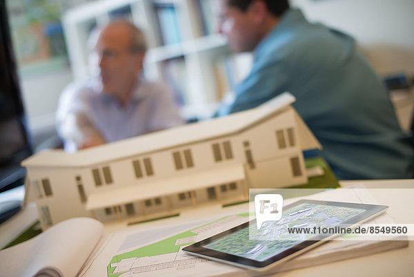 Architekten  die in einem Büro unter Einsatz von Computertechnologie an einem grünen Bauprojekt arbeiten. Das Modell eines Architekten für ein Haus. Computer-Tablett.