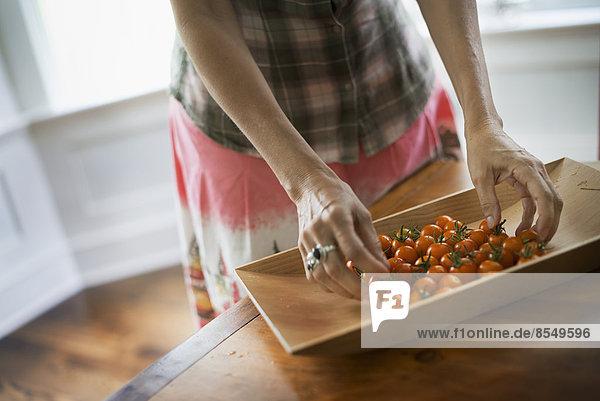 Biologische Erzeugnisse. Ein Tablett mit frisch gepflückten Bio-Tomaten in der Küche.