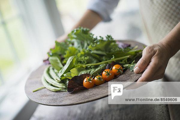 Eine Person  die in einer Küche frische Bio-Produkte zubereitet. Tablett mit Gemüse  Tomaten und Grünzeug.