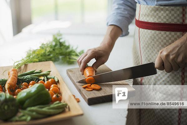 Eine Frau  die frisches Gemüse zubereitet. Sie schneidet eine Karotte in Scheiben.