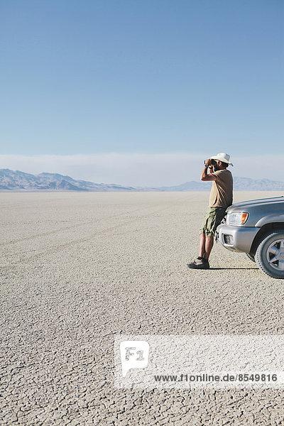 Ein Mann lehnt an einem Lastwagen und schaut durch ein Fernglas.