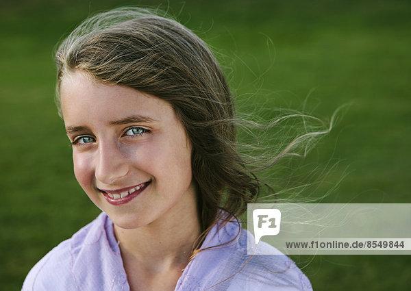 Porträt eines lächelnden neunjährigen Mädchens.