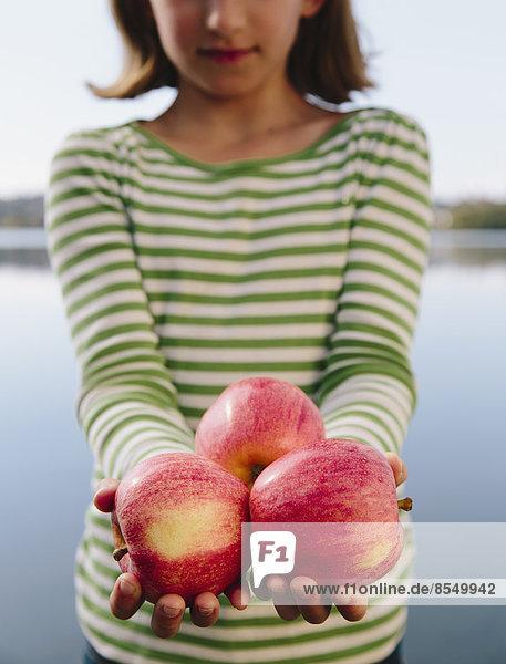 Neunjähriges Mädchen hält eine Handvoll Bio-Äpfel