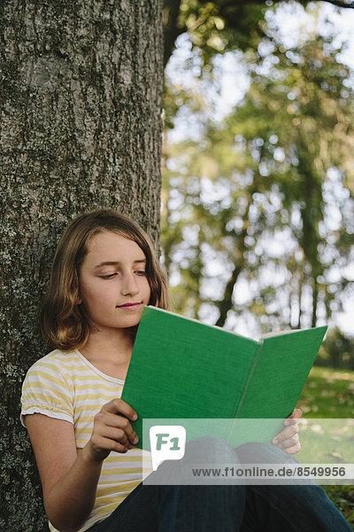 Neunjähriges Mädchen sitzt unter einem Baum und liest ein Buch