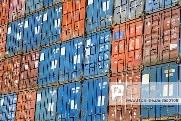 Ein Stapel von Frachtcontainern  kommerziellen Frachtcontainern  die zusammengepackt sind und darauf warten  bewegt zu werden.