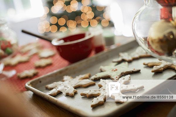 Backblech mit hausgemachten Bio-Weihnachtsplätzchen in Form von Eiszapfen und Sternen.