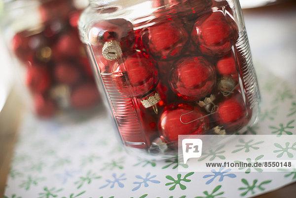 Roter Glaskugel-Weihnachtsschmuck in Glasgefäßen auf einer Tischplatte.