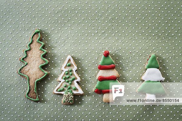 Hausgemachte Bio-Weihnachtsplätzchen in der Form von Weihnachtsbäumen  mit grüner  roter und weißer Glasur versehen.