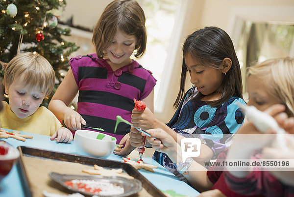A group of children  girls and boys  around a table  decorating organic Christmas cookies.